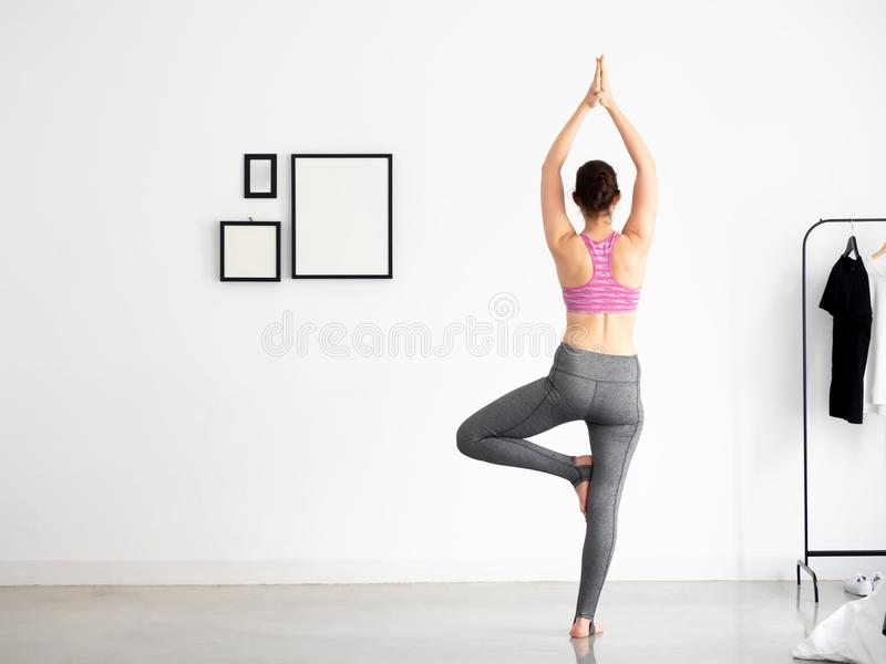 Back of Young beautiful caucasian sporty and active woman in sporty wear doing yoga position and meditating at home in white room royalty free stock photo