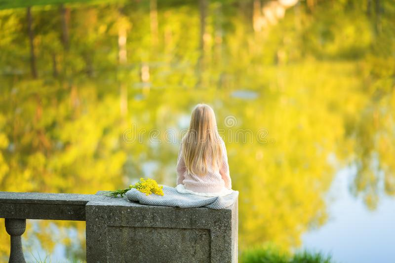 Back of young blond girl siiting on stone fence pier facing to lake view, watching sunset. Summer time. Copy space. loneliness royalty free stock photo