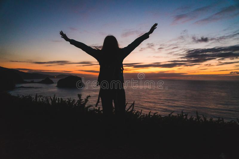Back of a young traveler girl standing on on the edge of a cliff by the ocean coast watching a beautiful sunset. Arms wide open. royalty free stock photo