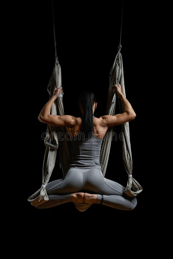 Back of young woman exercising aerial hammock yoga royalty free stock photo