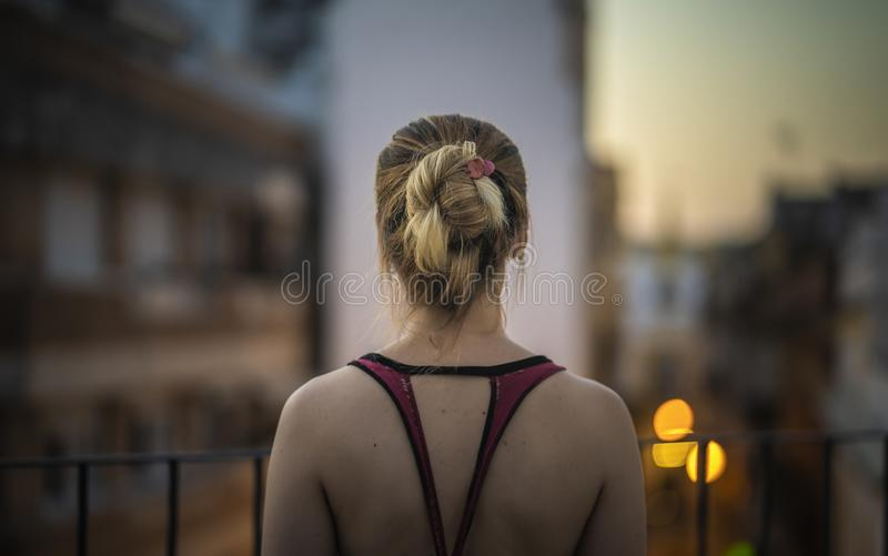 Young woman looking at the cityscape. Back of a young woman looking at the cityscape from a terrace at sunset royalty free stock photo