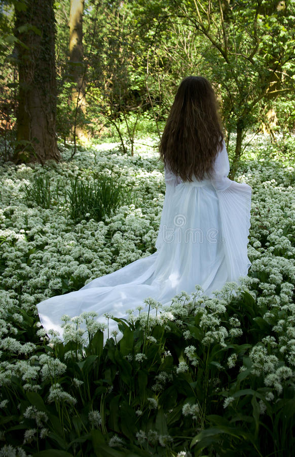 Back of a young woman wearing a long white dress stock image