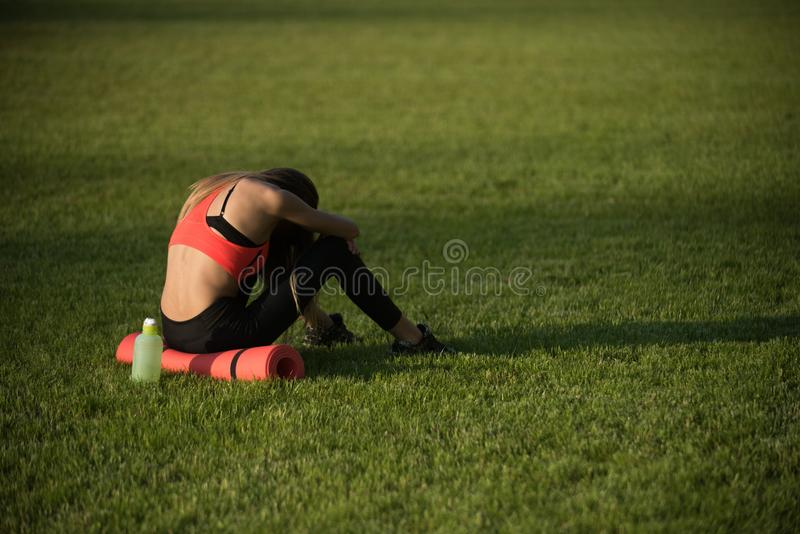 Backache, back pain, fatigue. Tired woman in sportswear relax after workout, training. Sportswoman sit on green grass with gym equipment on summer. Sport stock photos