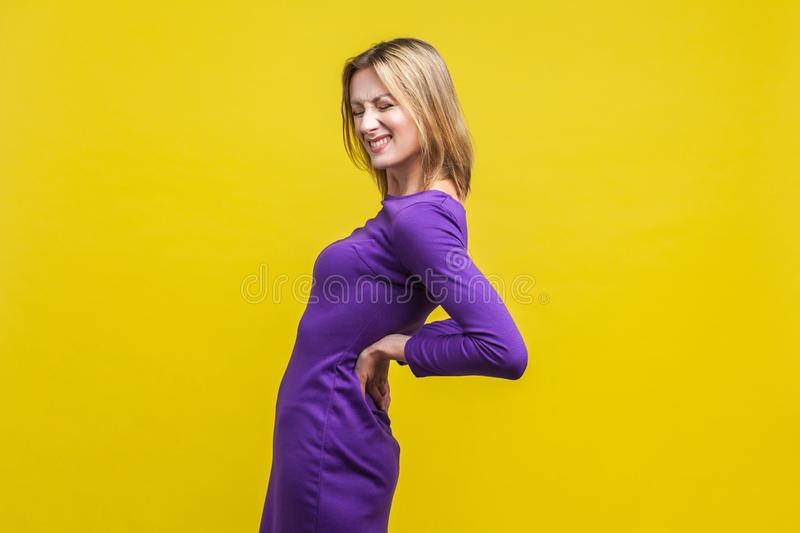 Backache. Portrait of young unhealthy woman suffering lower back pain. indoor studio shot  on yellow background royalty free stock photography