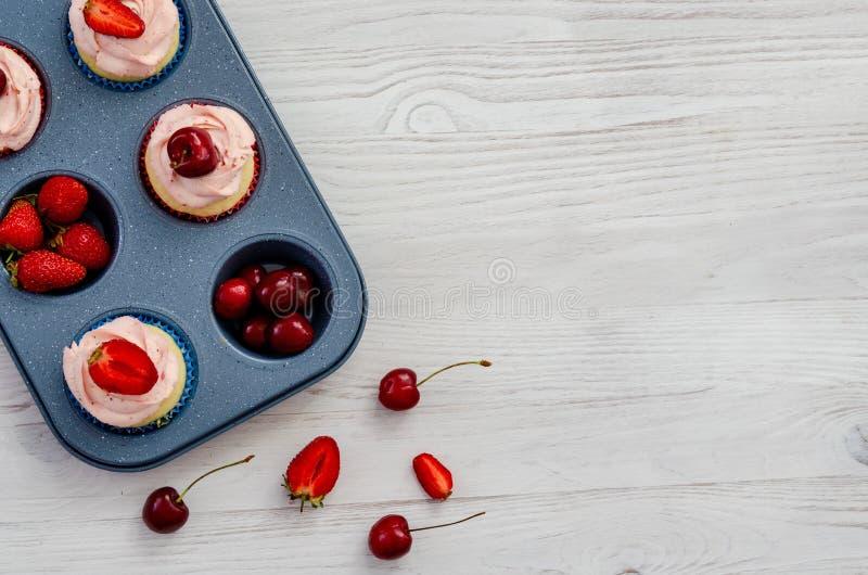Backblech mit Frucht und kleinen Kuchen auf einem weißen hölzernen Hintergrund stockfotos