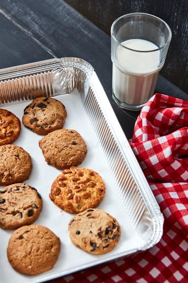 Backblech mit selbst gemachten Plätzchen für Sankt mit Erdnüssen, Schokoladensplittern, Rosinen und einem Glas mit Milch auf eine lizenzfreies stockbild