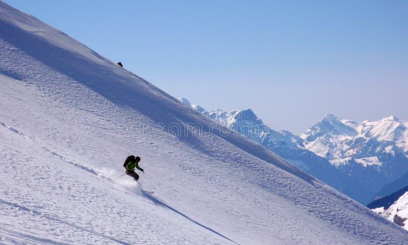 Backcountry skidåkare som skidar egentligen snabb down en orörd bergsida med påfyllningar av ny pulversnö fotografering för bildbyråer
