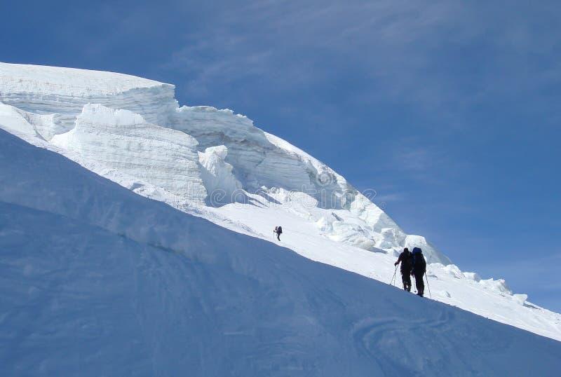 Backcountry skidåkare som upp fotvandrar en brant glaciär och in i solljuset på deras väg till ett högt alpint maximum nära Zerma arkivbild