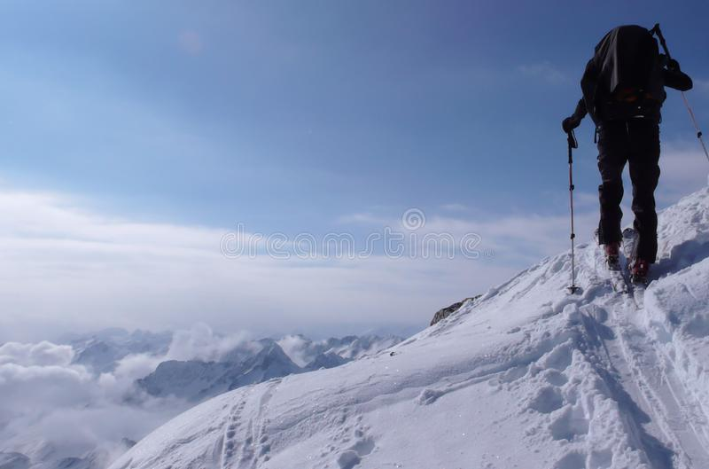 Backcountry skier hikes and climbs to a remote mountain peak in Switzerland on a beautiful winter day stock images