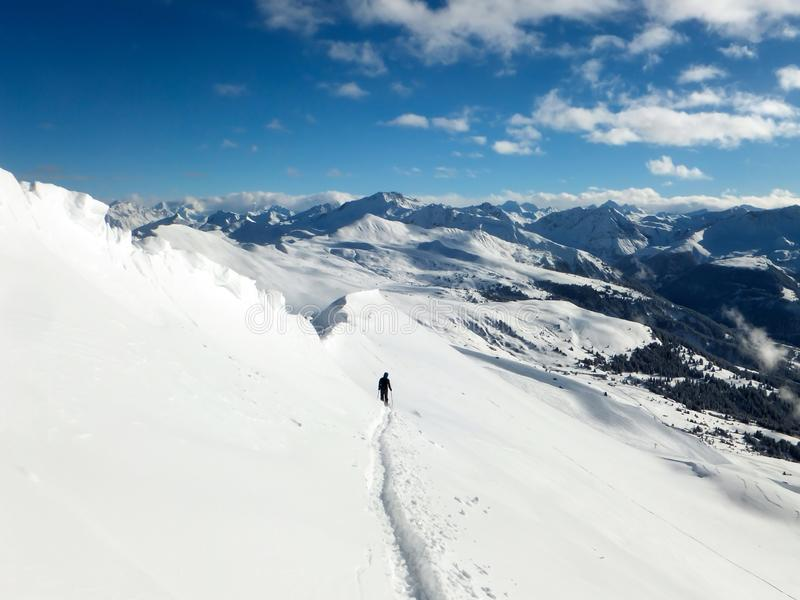 Backcountry skier enjoying a deep powder ski descent in the high Alps of Switzerland in deep winter near Arosa stock photo