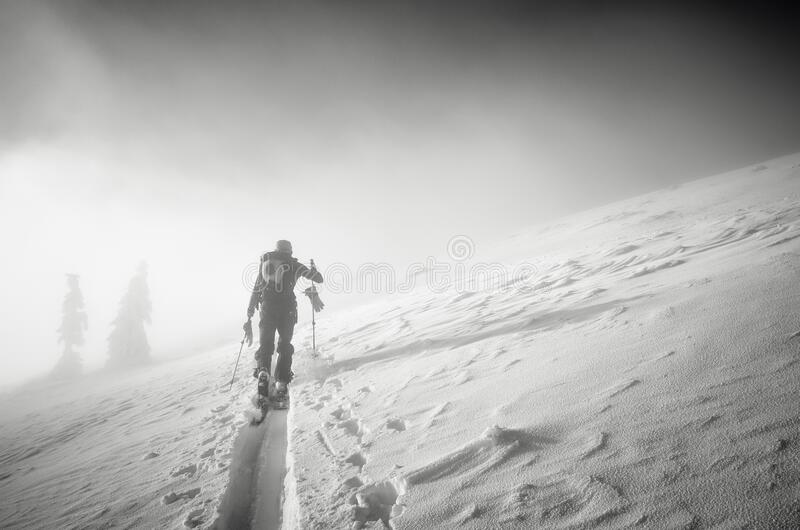 Backcountry skier pushing through the fog on a snowy slope. Black and white shot stock image