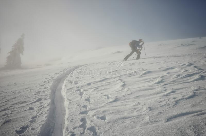 Backcountry skier pushing through the fog on a snowy slope. Blown by the wind stock images