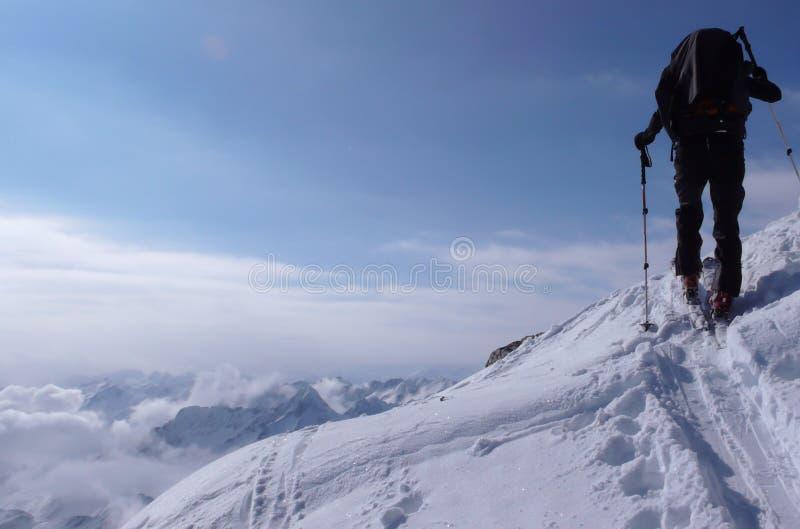 Backcountry-Skifahrerwanderungen und -aufstiege zu einer Fernbergspitze in der Schweiz an einem schönen Wintertag stockbilder