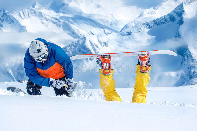 Backcountry snowboarder digging out his friend stock photos