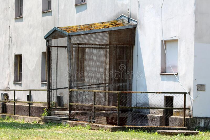 Backdoor entrance to large old industrial building protected with wire mesh and moss covered roof surrounded with rusted fence royalty free stock photo