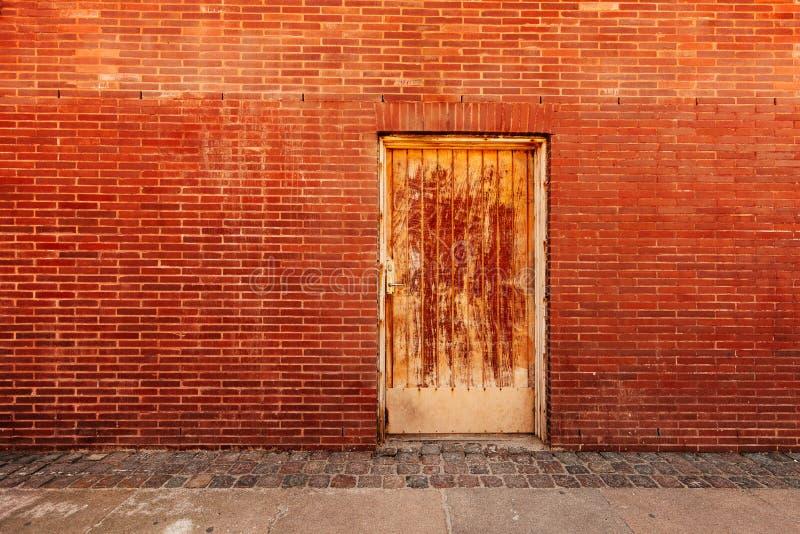 Backdoor, porta resistida velha e parede de tijolo fotos de stock royalty free