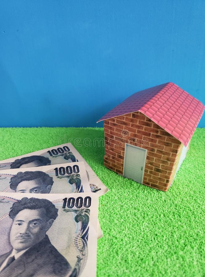 japanese banknotes and figure of a house on green surface and blue background royalty free stock image