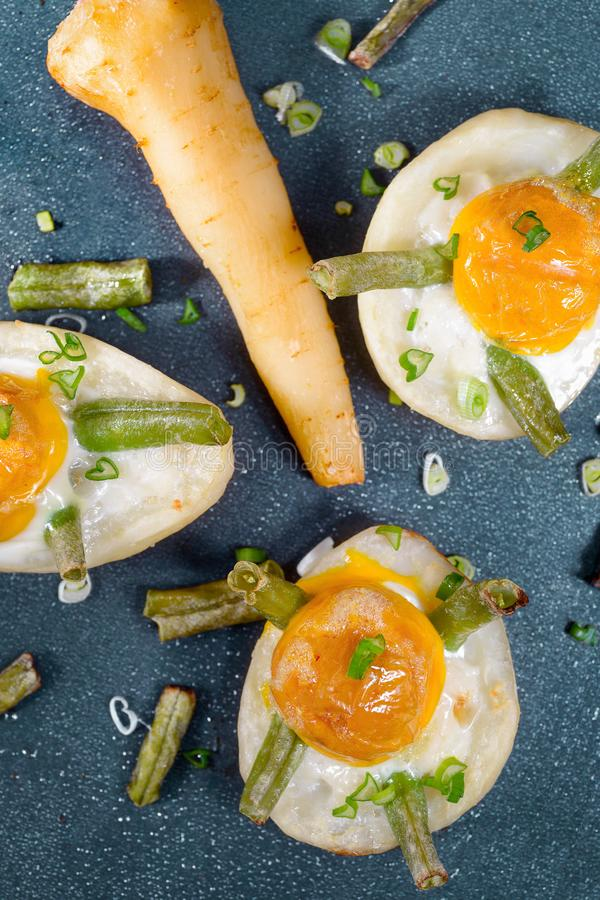 Backed potatoes with eggs, asparagus bean, celery and green onion stock photo