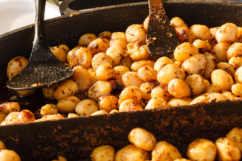 Backed young potatoes with spices in bowl stock images