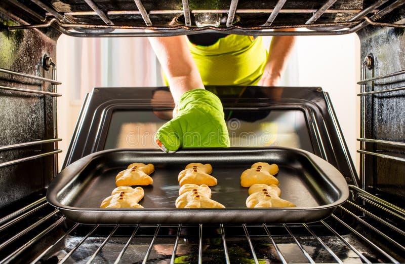 Backen-Lebkuchenmann im Ofen stockbilder