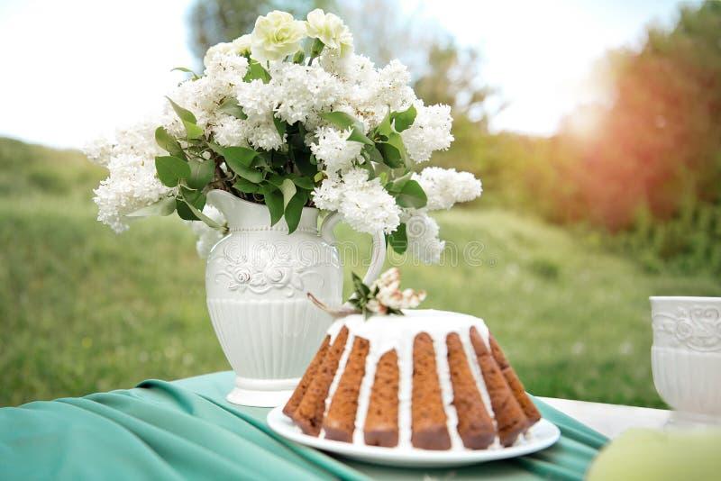 Backen Sie mit einigen Schalen auf dem Picknicktisch zusammen, der mit Blumen, Kerzen, Vase auf dem grünen Gebiet verziert wird stockbilder
