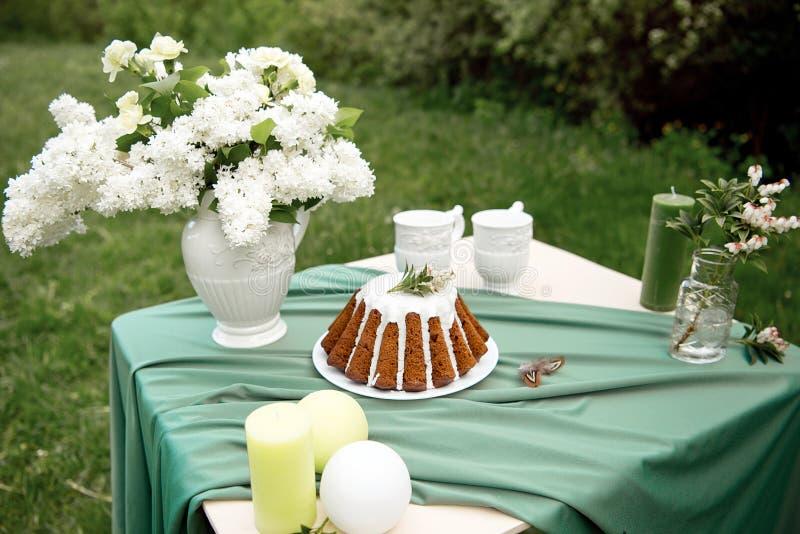 Backen Sie mit einigen Schalen auf dem Picknicktisch zusammen, der mit Blumen, Kerzen, Vase auf dem grünen Gebiet verziert wird stockbild