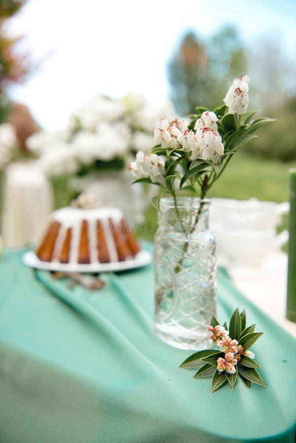 Backen Sie mit einigen Schalen auf dem Picknicktisch zusammen, der mit Blumen, Kerzen, Vase auf dem grünen Gebiet verziert wird lizenzfreie stockfotos