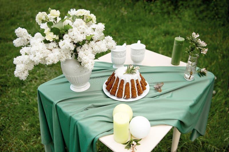 Backen Sie mit einigen Schalen auf dem Picknicktisch zusammen, der mit Blumen, Kerzen, Vase auf dem grünen Gebiet verziert wird stockfotos