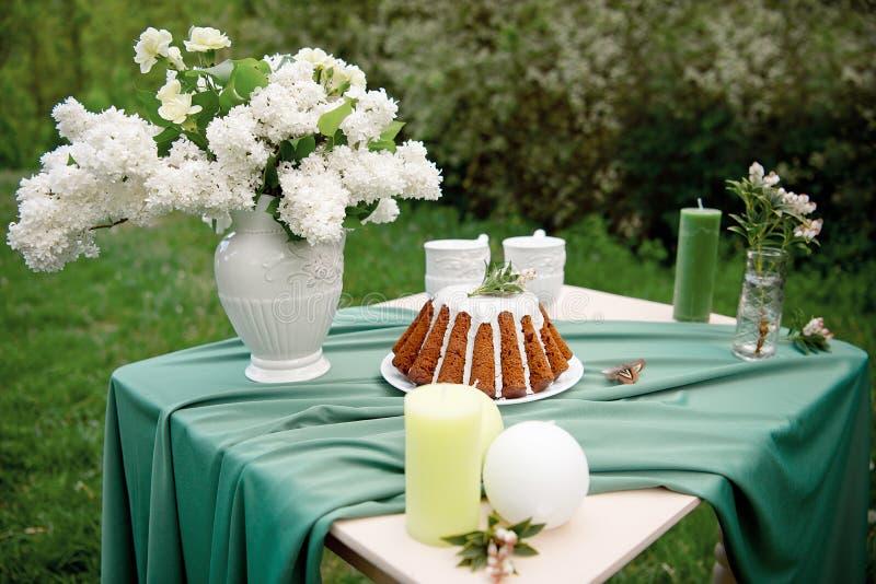 Backen Sie mit einigen Schalen auf dem Picknicktisch zusammen, der mit Blumen, Kerzen, Vase auf dem grünen Gebiet verziert wird lizenzfreie stockfotografie
