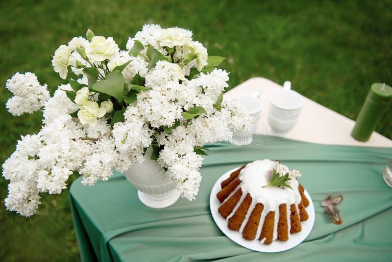 Backen Sie mit einigen Schalen auf dem Picknicktisch zusammen, der mit Blumen, Kerzen, Vase auf dem grünen Gebiet verziert wird stockfoto