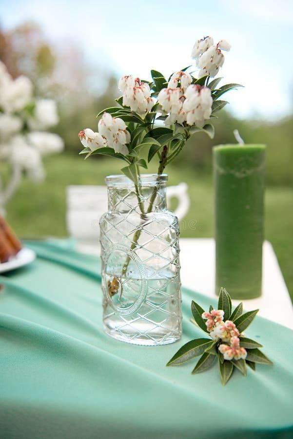 Backen Sie mit einigen Schalen auf dem Picknicktisch zusammen, der mit Blumen, Kerzen, Vase auf dem grünen Gebiet verziert wird lizenzfreies stockbild