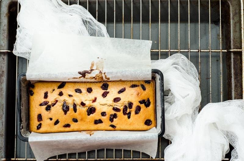 Backen Sie mit getrockneten Beeren in der Backform auf dem Gitter zusammen stockfoto