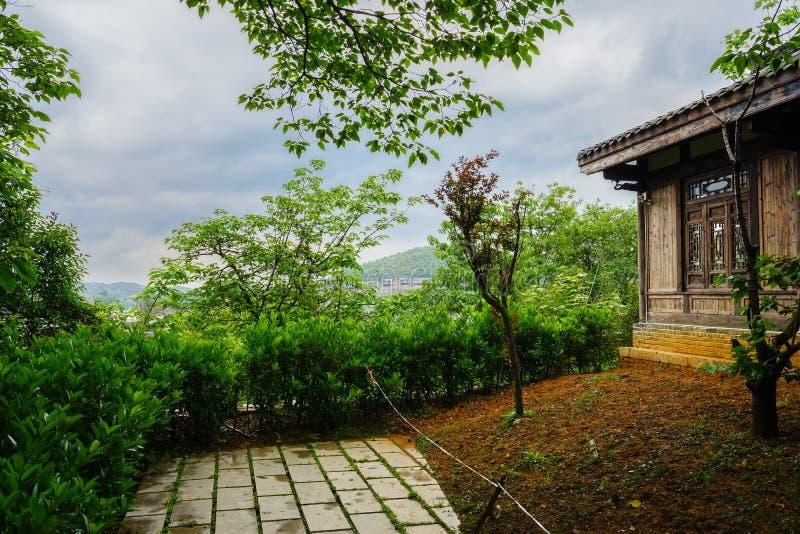 Backen tegelplatta-taklade träbyggnad vid banan i den molniga våren af royaltyfria foton
