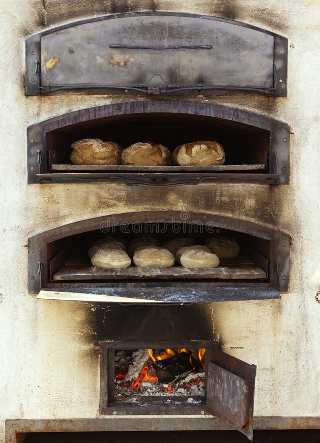 Backenbrot im traditionellen hölzernen Ofen lizenzfreie stockfotos