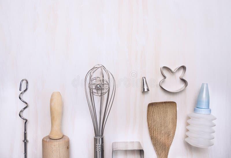 Backende gesetzte Geräte mit Nudelholz, Spachtel, wischen, gekerbter hölzerner Löffel auf weißem hölzernem Hintergrund, Draufsich lizenzfreie stockbilder