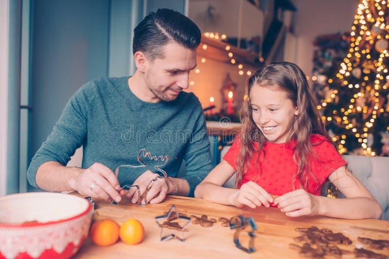 Backende Lebkuchenplätzchen der Familie auf Weihnachtsferien lizenzfreie stockfotos