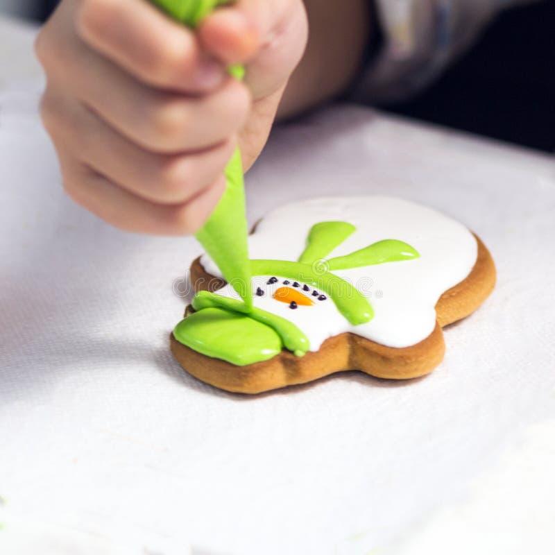 Backenfeiertagsplätzchen Kind übergibt die Verzierung des Lebkuchens in Form von ein Schneemann mit Puderzucker unter Verwendung  lizenzfreies stockbild
