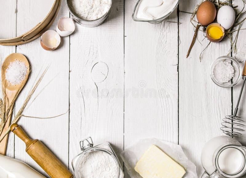 Backenhintergrund Bestandteile für den Teig - Milch, Eier, Mehl, Sauerrahm, Butter, Salz und verschiedene Werkzeuge lizenzfreie stockbilder