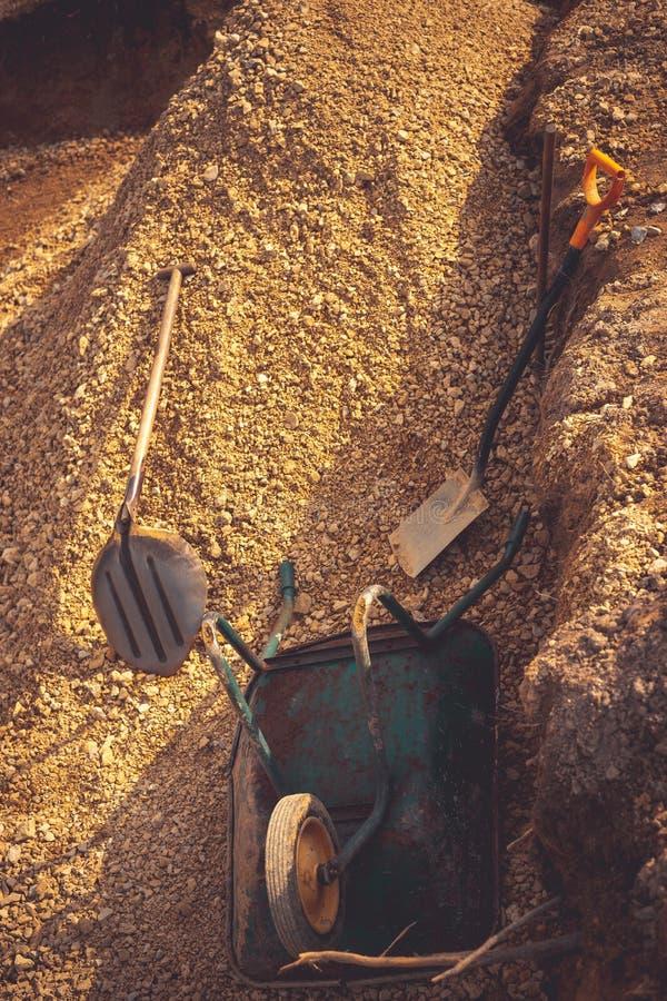 Backfilling av utgrävningen under fundamenttjock skiva Konstruktion, dolomite, skyfflar och skottkärra arkivbild