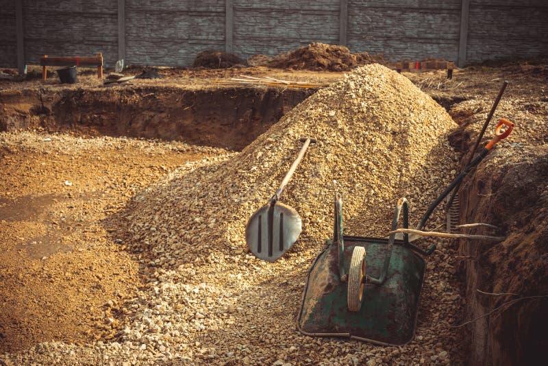 Backfilling av utgrävningen under fundamenttjock skiva Konstruktion, dolomite, skyfflar och skottkärra royaltyfria foton