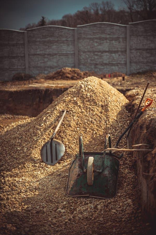 Backfilling av utgrävningen under fundamenttjock skiva Konstruktion, dolomite, skyfflar och skottkärra royaltyfri fotografi