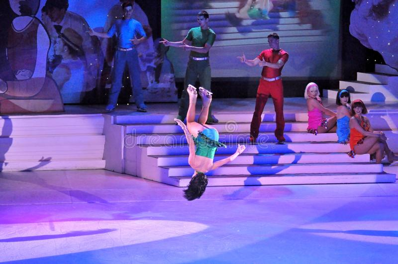 Backflip on ice. Professional sportsmans ice skaters performing in an ice show production onboard cruise ship Adventure of the Seas stock image
