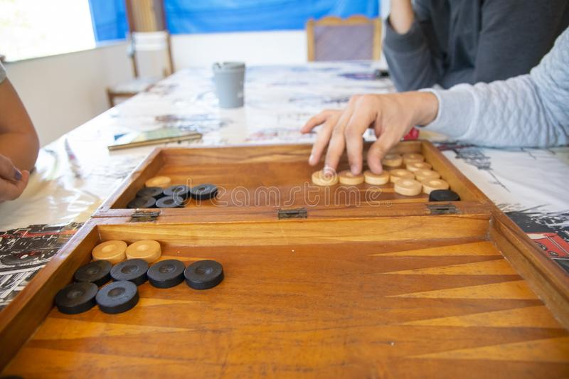 Backgammon game. The player`s hand moves the chip, closeup.  royalty free stock photos