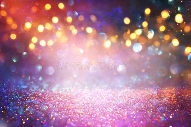 Background of abstract red, gold and purple glitter lights. defocused.  stock photo