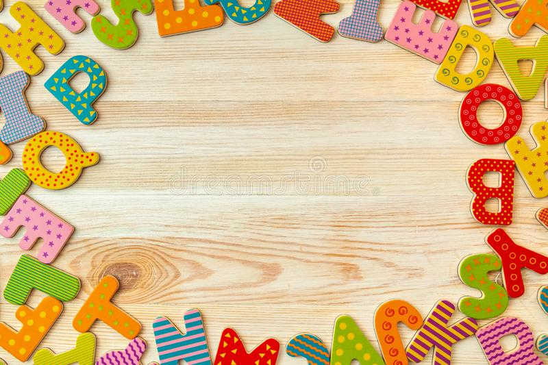 Background of alphabet letters. Top view abstraction of letters with copy space. Back to school concept. Colorful wooden letters of the alphabet on wooden stock photos