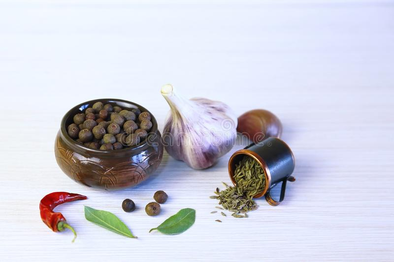 Background with aromatic spices. Seed of sweet-scented pepper in. A ceramic pot, garlic, bay leaf, chili and sprinkled cumin stock images
