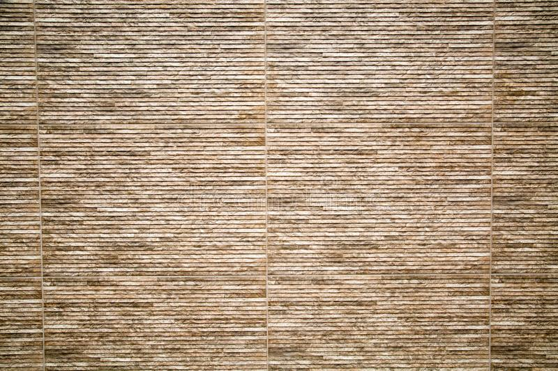 Background of artificial stone wall with horizontal stripes of brown and lilac color. stock images