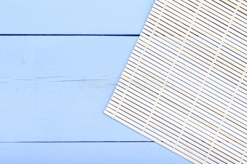 Background for asian restaurant. Bamboo mat on blue wooden table. Top view with copy space royalty free stock photography