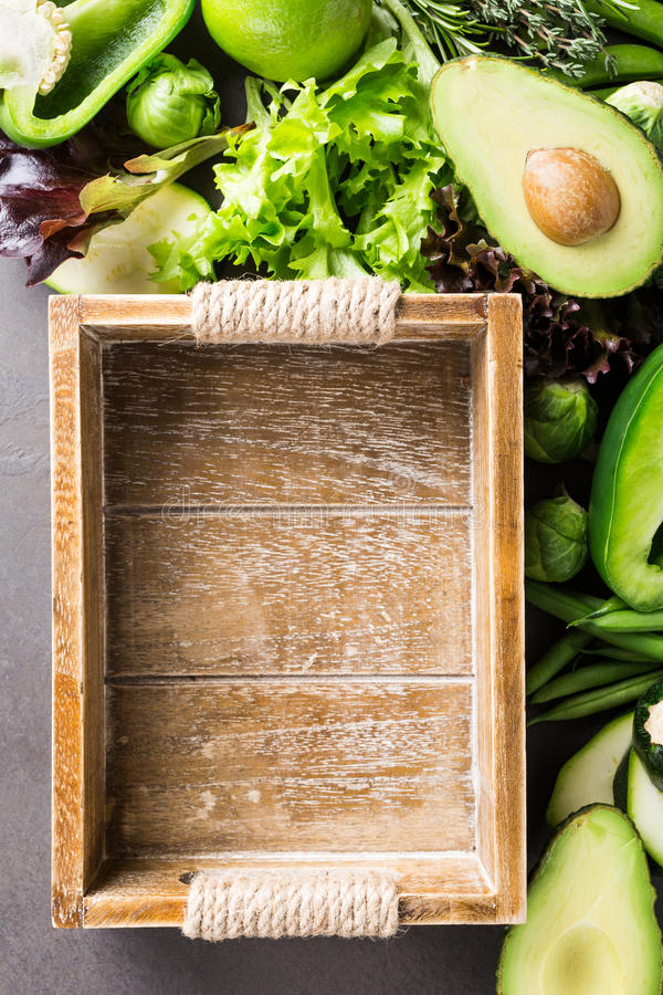 Background with assorted green vegetables. Salad, avocado, bell pepper and Brussels sprouts with wooden tray on light brown stone table top. Healthy food royalty free stock photography