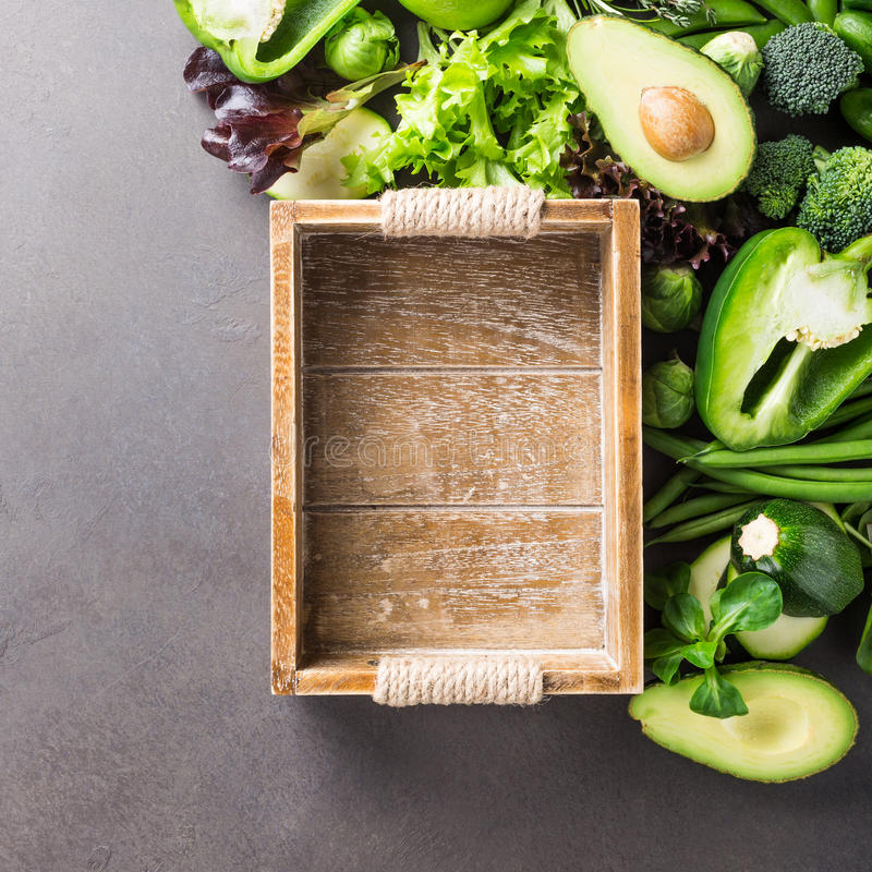 Background with assorted green vegetables. Salad, avocado, bell pepper and Brussels sprouts with wooden tray on light brown stone table top. Healthy food stock image